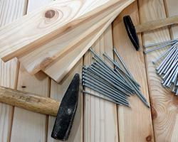 Picture of hammers, boards and nails on a wooden surface