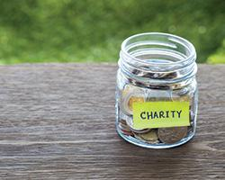 Glass jar containing coins with a sticky note on it that says Charity.